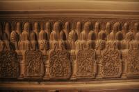 """Photo de détail d'une fresque de type """"orientalisme"""". Pierre gravée représentant une succession de petits totems"""