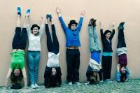 Photographie d'une bande de jeunes gens postant contre un mur bras levés ou faisant le poirier
