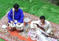 Photo de deux joueurs de musique indiens sur une pelouse, vus de haut