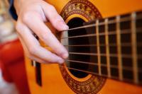 Une guitare dont on voit principalement les cordes. Une main est posée sur les cordes
