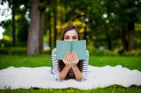 Photographie d'une jeune femme lisant sur l'herbe