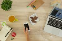 Une photo prise de haut où il y a un ordinateur, un café, un cahier et un stylo. Quelqu'un tient un smartphone dans sa main, on ne voit que sa main.