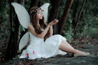 femme habillée en ange assise à côté d'un arbre