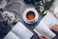 Une mise en scène avec un thé, des bouquets de fleurs et les mains de quelqu'un qui tiennent un livre.