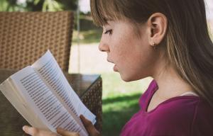 une jeune fille lit un livre dans un jardin