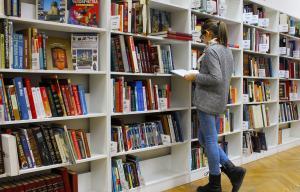 une jeune fille lit un livre devant un rayonnage de livres
