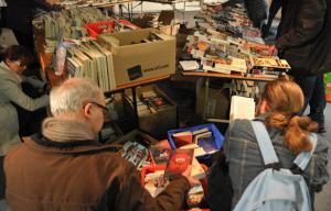Photo de la braderie à la Médiathèque avec des étals de livres et des gens qui sont en train de les regarder