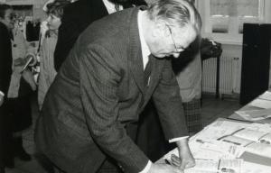 André Diligent en train de signer un contrat habillé en costume
