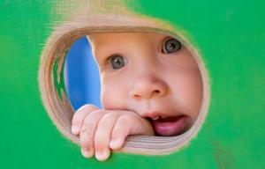 Un bébé passe sa main et sa tête par un trou fait sur une cloison verte