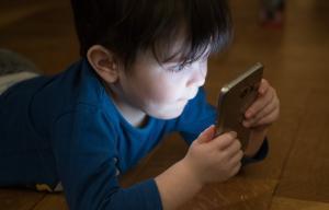 Un enfant allongé sur le ventre est absorbé par l'écran d'un téléphone