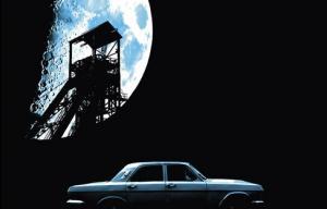 Photographie très sombre d'une voiture, d'un élément de paysage industriel et d'une lune