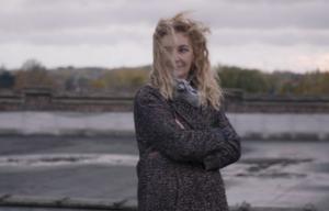 Photo de Corinne Masiero cheveux au vent dans un paysage gris