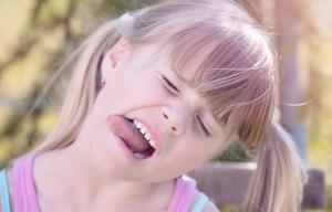 Une petite fille avec des couettes penche la tête et tire la langue
