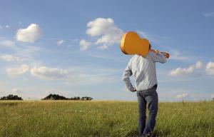 Photo d'une personne de dos qui marche dans un champ, dont la tête est cachée par une guitare