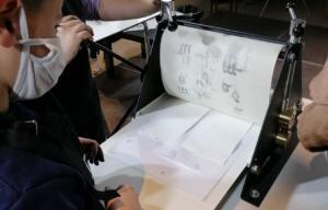 un enfant à côté d'une presse voit apparaître sa gravure