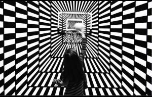 Un fond noir et blanc avec des carreaux qui provoque une illusion d'optique et une petite fille qui joue au basket sur ce fond