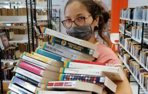 Une femme tient une grosse pile de livres dans ses bras