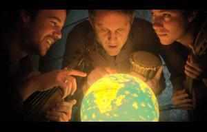 Photographie du groupe Baya Trio : trois hommes penchés sur un globe terrestre lumineux