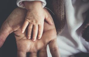 Une grande main d'adulte sur laquelle est posée une petite main d'enfant