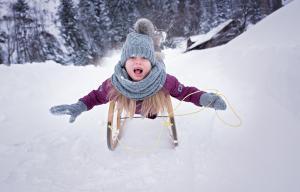 un enfant fait de la luge et semble crier de joie