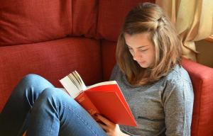 ado qui lit un livre assise dans un canapé rouge