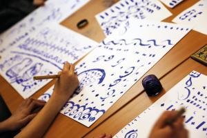 Photographie représentant des mains en train de pratiquer la calligraphie