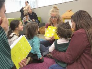 Photographie de parents avec leurs enfants en train d'écouter une animatrice au centre qui lit une histoire