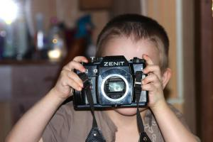Un petit garçon tient un appareil photo devant ses yeux