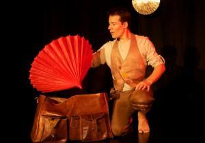 Un homme sur scène qui sort un parapluie rouge d'une valise