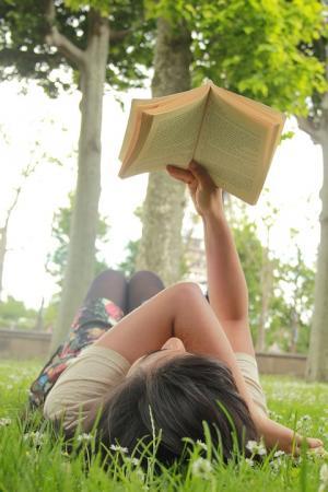 visuel d'une jeune fille lisant allongée dans l'herbe en train de lire