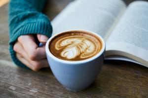 Quelqu'un lit un livre avec une tasse de café dans la main