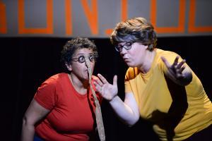 Deux femmes sur scène, l'une est habillée en rouge, l'autre en jaune. Celle en jaune fait des grands gestes, l'autre l'observe