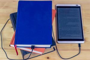 Photographie d'une liseuse connectée par un cable à un livre papier