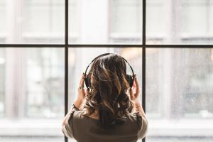 Une jeune fille devant une fenêtre écoute de la musique avec un casque audio