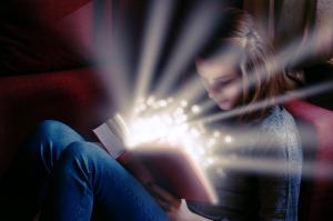 Une jeune fille lit un livre qui s'illumine et qui paraît magique