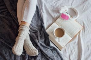 Photo de jambes sur un lit avec un livre et une tasse de café