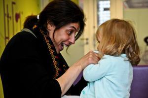 Photo représentant une adulte en train de chatouiller le menton d'une petite fille (photo prise durant une séance de comptine à la médiathèque de Roubaix)