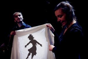 Un homme et une femme tienne un drap sur lequel une ombre est projetée