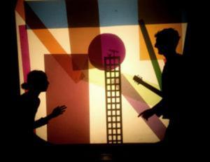 Une image du spectacle représentant deux enfants en ombres autour d'un ballon rouge