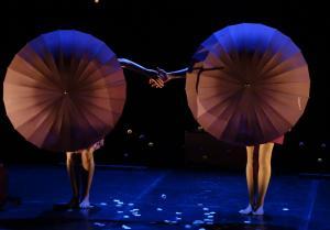 Deux femmes se tiennent la main et deux gros parapluies leur cachent le visage
