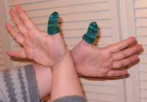 Photographie de deux mains ayant leur pouce déguisées en sapin de Noel