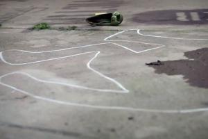 Photo de bitume avec des traces de craie, une chaussure et une tache sombre sur le sol