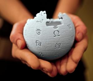 mains tenant le symbole de wikipedia en relief
