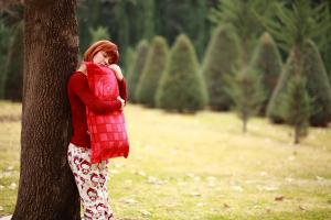 Une jeune fille se tient contre un arbre, elle est habillée en rouge et tient un oreiller rouge dans ses bras
