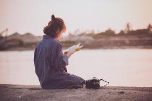 Une jeune fille lit un livre assise sur le rebord d'un canal