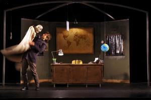 Sur scène, un homme fait virevolter une grande marionnette
